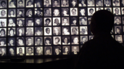A visitor looks at the faces of some of the victims of the Oklahoma City bombing at the Oklahoma National Memorial museum in Oklahoma City June 12, 2001, one day after the execution of Timothy McVeigh. (Photo by Joe Raedle/Getty Images)