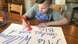 Sam Gertner, 6th grade, makes a sign with his teacher's name on it.